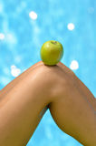Summer healthy diet concept. Summer healthy diet apple concept. Apple temptation on woman leg on water pool background Stock Image