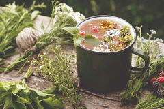 Summer healthy herbal tea in old enameled mug and bunches of healing herbs on wooden board. Herbal medicine. Retro toned photo stock photos