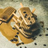 Flatlay of melting coffee latte popsicles with coffee beans. Summer healthy vegan frozen dessert. Flatlay of melting coffee latte popsicles with coffee beans stock photography