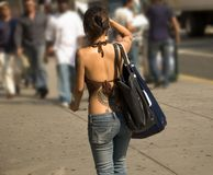 Summer Heat. This is a shot of a young lady with several tattoos walking in the city on a hot summer day royalty free stock images