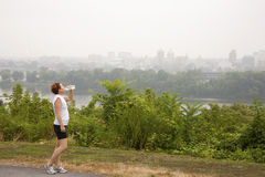 Summer Heat. Woman jogger stopping for a drink of water on a running path overlooking the skyline of a river city Royalty Free Stock Image