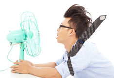 Summer heat, business man use fans to cool down. In studio Stock Images