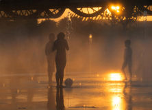 Summer Heat. Unrecognizable young kids scape from the summer heat wave at dusk playing with the water jets in the fountains of the recently renovated Madrid Río Stock Image