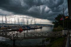 A thunderstorn is emerging over a small port at lake constance royalty free stock image