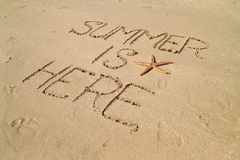 Summer is here. Written in beach sand with starfish Stock Image