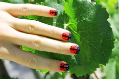 Summer Is Here. Creative nail art - ladybugs seating on a green leaf. Close-up of a female hand with colorful nails Stock Photo