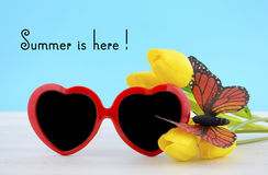 Summer Is Here concept with red heart shape sunglasses. With butterfly on yellow flowers on white wood table and sky blue background Stock Photo