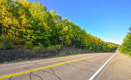 Summer highway open road to anywhere.  Sunny blue sky, woods on either side down a country highway in summer. Stock Photo