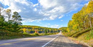 Summer highway open road to anywhere.  Sunny blue sky, woods on either side down a country highway in summer. Royalty Free Stock Photos