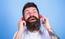Summer hit concept. Man bearded hipster red ripe strawberry ears as headphones. Summer top radio chart. Guy enjoy juicy. Sound summer hit song music. Hipster Royalty Free Stock Photography