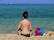 Summer holiday. Woman sitting and relaxing near sea, colourfol ball beside Stock Images
