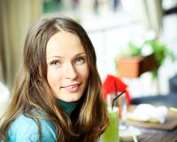 Summer holiday. Young smiling woman in summer cafe. Shallow depth of field royalty free stock photos