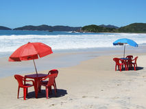 Summer holiday. Two tables with chairs and sunshade on a tropical beach Stock Photos