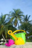 Summer holiday. Summer vacation conceptual with child's bucket, spade and other toys on tropical beach Stock Image