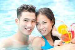 Summer holiday. Young happy couple in swimming pool with cocktails looking at camera Stock Image