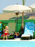 Summer holiday. Swimming pool with charis and beach umbrella stock photography