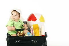 Summer Holiday. Baby sitting in a bag packed with beachy things royalty free stock photography