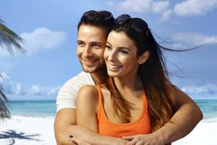 Summer holiday. Young couple hugging on the beach, having fun, enjoying summer holiday, looking away Royalty Free Stock Photo