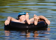 Summer Holiday. The boy enjoys his summer holiday floating on a tube in a lake Royalty Free Stock Photos