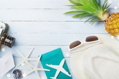 Summer holiday accessories from sunglasses, hat, passport, retro camera, airplane and boat miniatures, starfish. Travel concept. Royalty Free Stock Image