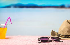 Summer holiday background with free empty blank copy space. Brimmed hat, sunglasses and yellow drink on towel in paradise lagoon.