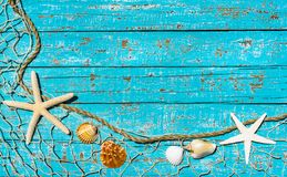 Summer holiday background, maritime fishing net with starfish and seashells on turquoise blue wood. Starfish and Seashells in fishing net on turquoise wooden royalty free stock photo