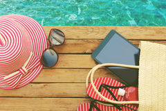 Summer holiday bag with tablet and flip flops on wooden deck. View from above. Summer holiday bag with tablet and flip flops on wooden deck Royalty Free Stock Photo