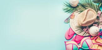 Summer holiday banner. Beach accessories : straw hat, palm leaves, sun glasses, pink flip flops , bikini and coconut cocktail on. Blue turquoise background, top stock photography