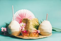 Summer holiday . Beach accessories : straw hat, palm leaves, pink sun glasses, flowers and coconut cocktails on blue turquoise. Background, front view. Tropical royalty free stock photo