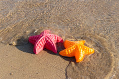 Summer Holiday, Beach Waves Starfish and colored toys Stock Photography