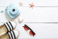 Summer holiday composition, traveler accessories on white wooden desk: sunglasses, sandals, instant camera, sea shell and star. Va. Cation, relaxing, sea beach royalty free stock photography