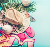 Summer holiday concept. Beach accessories : straw hat, palm leaves, sun glasses, pink flip flops , bikini and coconut cocktail. On blue turquoise background royalty free stock photo