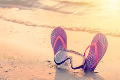 Summer holiday concept. Colorful flip flops with diving mask on the sandy beach during sunset. Toned.  stock image