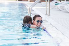 Happy mother and her daughter playing in swimming pool royalty free stock photography