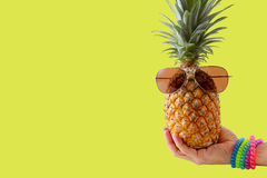 Summer and Holiday concept.Hipster hand holding Pineapple Fashio. N Accessories and Fruits on yellow background Royalty Free Stock Photo