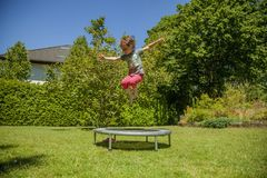 Summer holiday concept. Little cute child girl having fun outdoors and she jumping on a trampoline