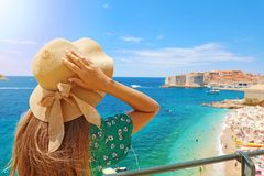 Summer holiday in Croatia. Back view of young woman holding her hat with Dubrovnik town on the background, Croatia, Europe royalty free stock image