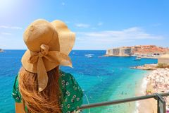 Summer holiday in Croatia. Back view of young woman with straw hat and green dress with Dubrovnik old town on the background, stock photo
