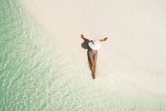 Free Summer Holiday Fashion Concept - Tanning Girl Wearing Sun Hat At The Beach On A White Sand Shot From Above.Top View From Drone. Royalty Free Stock Images - 164486819