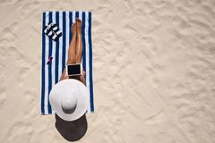 Summer holiday fashion concept - tanning woman wearing sun hat a. T the beach on a white sand shot from above Stock Photography