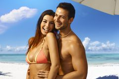 Summer holiday. Happy young loving couple on summer holiday, embracing and smiling on the beach Stock Images