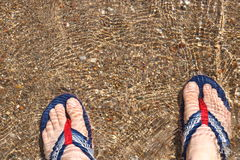 Summer holiday. Hawaii slipper foot sea sand wave baeach pebble rock Royalty Free Stock Images