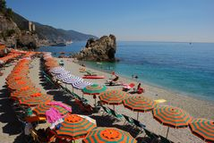 Summer Holiday on Italian Riviera with bright orange green umbrella. Rows of Colorful Umbrellas on Italian Riviera with many tourists and locals sunbathing stock photography
