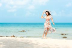 Summer Holiday. Lifestyle smiling asian woman wearing dress fashion summer trips relax on the sandy ocean beach. Happy woman enjoy stock image