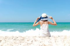 Summer Holiday. Lifestyle woman white dress wearing fashion summer trips sitting on the sandy ocean beach. Happy woman enjoy and r royalty free stock photography