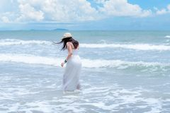 Summer Holiday. Lifestyle woman white dress wearing fashion summer trips walking on the sandy ocean beach. Happy woman enjoy and r stock image