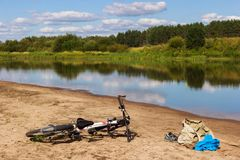 Bicycle camping on the river beach. Hot summer day for swim, nature landscape and reflections in the water royalty free stock photo