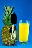 Summer holiday, cold pineapple juice, sunglasses, pearl decoration, on the beach. royalty free stock photos