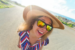 Summer, holiday, selfie and vacation concept - Young woman making funny face at summer day wearing hat and sunglasses Royalty Free Stock Images