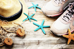 Summer holiday setting with straw hat and seashells Stock Images
